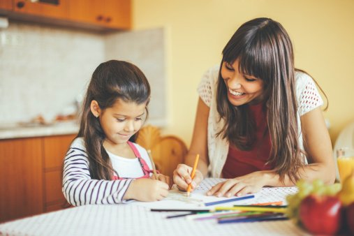 Mom and young daughter working through schoolwork together at home on kitchen table