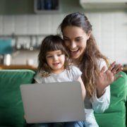 Happy mother and kid daughter waving hands looking at web camera using laptop for video call